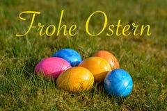 Szczęśliwa wielkanoc w niemiec z kilka kolorowymi Wielkanocnymi jajkami kłama o zdjęcia stock