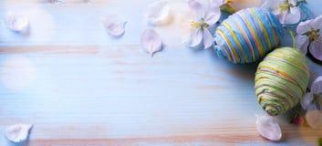Szczęśliwa wielkanoc; Wielkanocni jajka i sprig kwiaty na błękicie zgłaszają backg Obrazy Stock