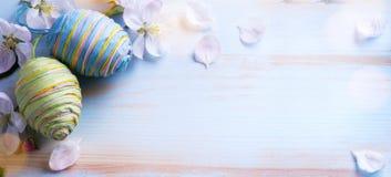 Szczęśliwa wielkanoc; Wielkanocni jajka i sprig kwiaty na błękicie zgłaszają backg Obraz Stock