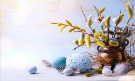 Szczęśliwa wielkanoc; Wielkanocni jajka i sprig kwiaty na błękitnym tle Zdjęcia Stock