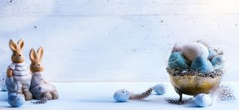Szczęśliwa wielkanoc; Wielkanocni jajka i Wielkanocny królik na błękicie zgłaszają backgr Zdjęcia Royalty Free