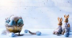 Szczęśliwa wielkanoc; Wielkanocni jajka i Wielkanocny królik na błękita stole Obraz Royalty Free