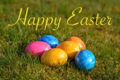Szczęśliwa wielkanoc z kilka kolorowymi Wielkanocnymi jajkami kłama na trawie obraz royalty free