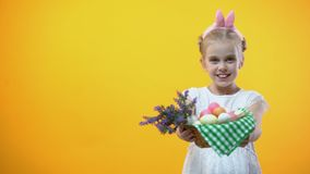 Szczęśliwa Wielkanocna inskrypcja, uśmiechnięta mała dziewczynka pokazuje kosz z jajkami, wita zbiory