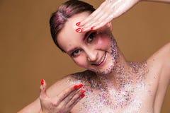 Szczęśliwa wzorcowa kobieta z modnym błyskotliwość makijażem pokazuje ona gwoździe obrazy stock