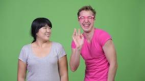 Szczęśliwa z nadwagą Azjatycka kobieta i potomstwo homoseksualista ono uśmiecha się wpólnie zbiory