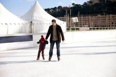 Szczęśliwa z podnieceniem chłopiec i jego młody ojca uczenie lód Obrazy Stock