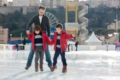 Szczęśliwa z podnieceniem chłopiec i jego młody ojca uczenie lód Fotografia Royalty Free