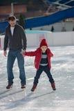 Szczęśliwa z podnieceniem chłopiec i jego młody ojca uczenie lód Zdjęcie Royalty Free