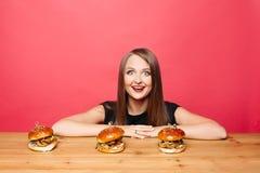 Szczęśliwa z podnieceniem kobieta ono uśmiecha się przy kamerą z hamburgerami na stole przed ona Zdjęcie Royalty Free