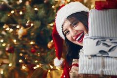 Szczęśliwa z podnieceniem kobieta trzyma wiele prezentów pudełka z bo w Santa kapeluszu Fotografia Royalty Free