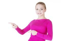 Szczęśliwa, z podnieceniem młoda kobieta wskazuje na kopii przestrzeni, obrazy royalty free