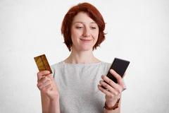 Szczęśliwa zadowolona kobieta z krótkim włosy chwyty mądrze telefon i klingeryt karta, sprawdza jej konto bankowe, satysfakcjonuj obraz stock