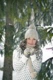 Szczęśliwa, zadziwiająca, przestrasząca, szczęsliwa, urocza dziewczyna w zimie lasowej, trzyma jej rękę z i ono uśmiecha się ciep Zdjęcia Royalty Free