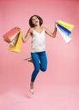 Szczęśliwa zakupy kobieta skacze up z wiązką torba na zakupy fotografia stock