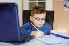 Szczęśliwa zdrowa dzieciak chłopiec z szkłami robi szkolnej pracie domowej z notatnikiem w domu Zainteresowany dziecko pisze esej fotografia stock