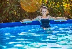 Szczęśliwa zdrowa kobieta w błękitnym swimwear w pływackiego basenu relaksować zdjęcia royalty free