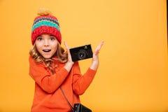 Szczęśliwa zdziwiona młoda dziewczyna w pulowerze i hatholding retro kamerze Obraz Royalty Free