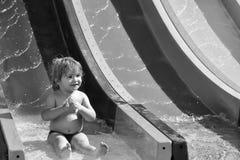 Szczęśliwe śliczne chłopiec przejażdżki od waterslide Zdjęcie Stock