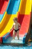 Szczęśliwe śliczne chłopiec przejażdżki od waterslide Zdjęcia Stock