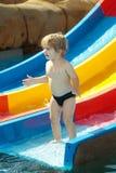 Szczęśliwe śliczne chłopiec przejażdżki od waterslide Zdjęcie Royalty Free
