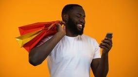 Szczęśliwe amerykanina mężczyzny mienia torby na zakupy i smartphone, online zakup zbiory