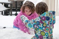 Szczęśliwe berbecia rodzeństwa dziewczyny w ciepłym żakiecie, trykotowy kapeluszowy podrzucać w górę śniegu outside i mieć zabawę obraz stock