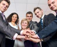 Szczęśliwe biznes drużyny organizowania ręki i ono uśmiecha się obrazy royalty free