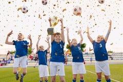 Szczęśliwe chłopiec Świętuje piłki nożnej mistrzostwo Młodości Wygranej drużyny Futbolowy doskakiwanie i wydźwignięcie Złota fili zdjęcia royalty free