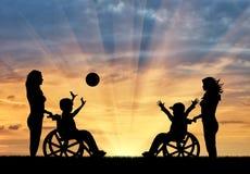 Szczęśliwe chłopiec w wózku inwalidzkim bawić się piłkę i pielęgnują zmierzch Zdjęcia Stock