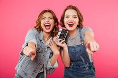 Szczęśliwe damy robią fotografii i wskazywać kamerą wy Zdjęcie Stock