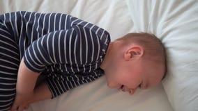Szczęśliwe dziecko leżące na łóżku na biaÅ'ym arkuszu w zwolnionym tempie zdjęcie wideo