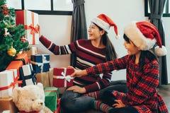 Szczęśliwe dziewczyny dekorują żywego izbowego położenie prezenta pudełko zdjęcia royalty free