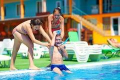 Szczęśliwe dziewczyny pchają faceta w basen wodzie zdjęcia stock