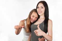Szczęśliwe dziewczyny uśmiechają się przedstawienie kciuk up podpisują wy Fotografia Stock
