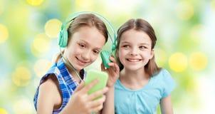 Szczęśliwe dziewczyny z smartphone i hełmofonami Zdjęcie Stock