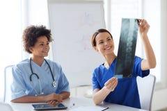 Szczęśliwe kobiet lekarki z promieniowanie rentgenowskie wizerunkiem przy szpitalem Zdjęcie Royalty Free