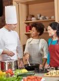 Szczęśliwe kobiety i szefa kuchni kucbarski kucharstwo w kuchni Zdjęcie Royalty Free