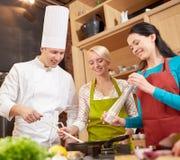 Szczęśliwe kobiety i szefa kuchni kucbarski kucharstwo w kuchni Fotografia Stock