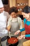 Szczęśliwe kobiety i szefa kuchni kucbarski kucharstwo w kuchni Zdjęcia Royalty Free
