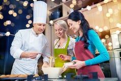Szczęśliwe kobiety i szefa kuchni kucbarski pieczenie w kuchni zdjęcie royalty free