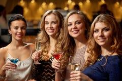Szczęśliwe kobiety piją w szkłach przy noc klubem obrazy royalty free