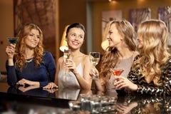 Szczęśliwe kobiety piją w szkłach przy noc klubem obrazy stock