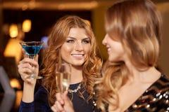 Szczęśliwe kobiety piją w szkłach przy noc klubem zdjęcia stock