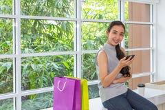 Szczęśliwe kobiety używa telefonu komórkowego i pastylki obsiadanie w sklepie z kawą Żeński działanie z pastylką używać ogólnospo obrazy royalty free