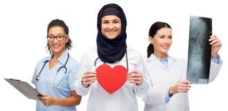 Szczęśliwe lekarki z czerwonym sercem, promieniowaniem rentgenowskim i schowkiem, Zdjęcia Royalty Free