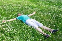 Szczęśliwe mężczyzna lying on the beach ręki szeroko rozpościerać na zielonej łące Obrazy Royalty Free
