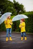 Szczęśliwe młode chłopiec, bracia z parasolami, podeszczowi żakiety i buty chodzi w wiosna parku przy deszczowym dniem, obrazy royalty free