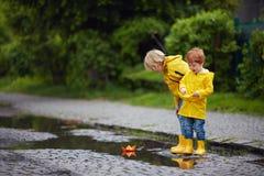 Szczęśliwe młode chłopiec, przyjaciele bawić się w wiosen kałużach z kolorowymi papierowymi łodziami obrazy royalty free