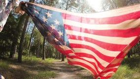 Szczęśliwe młode kobiety biegać z amerykańską flagą państowową